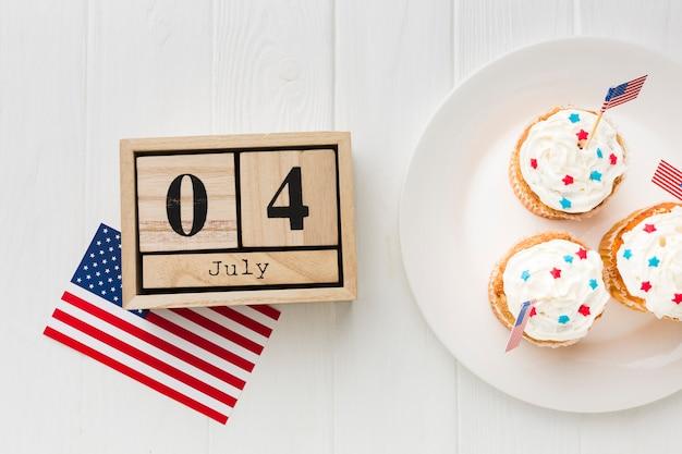 アメリカの国旗と日付のプレートにカップケーキのトップビュー