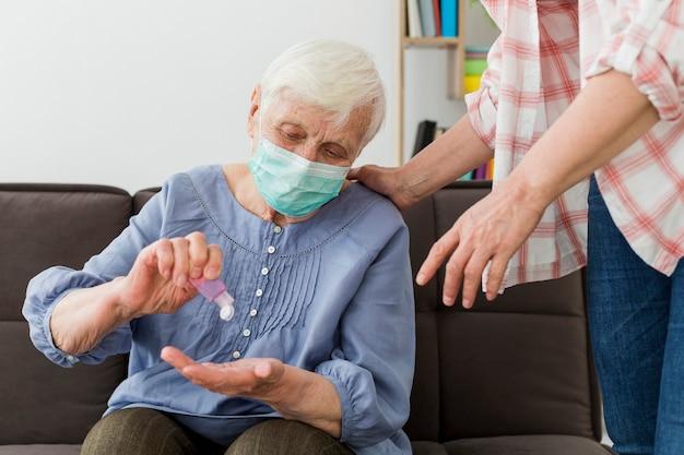 Вид спереди пожилой женщины, используя дезинфицирующее средство для рук при ношении медицинской маски