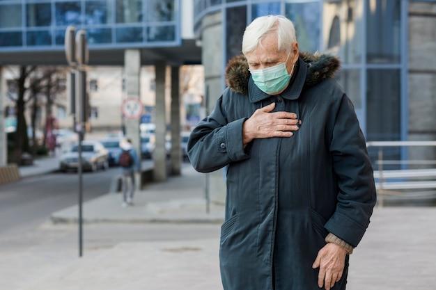 市内にいる間気分が悪く医療用マスクを持つ高齢者の女性の正面図