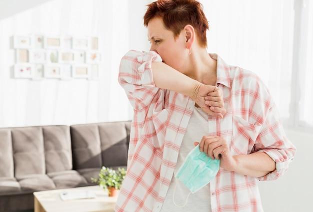 肘で咳をする高齢者の女性の正面図