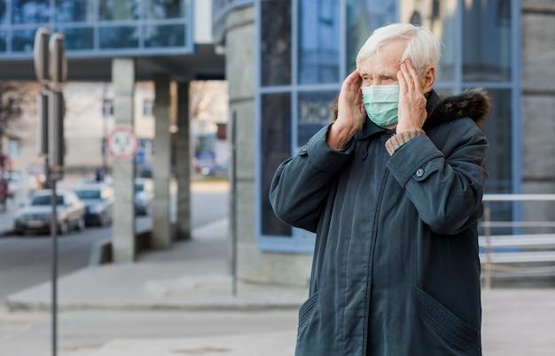 Вид спереди старшей женщины в городе в медицинской маске