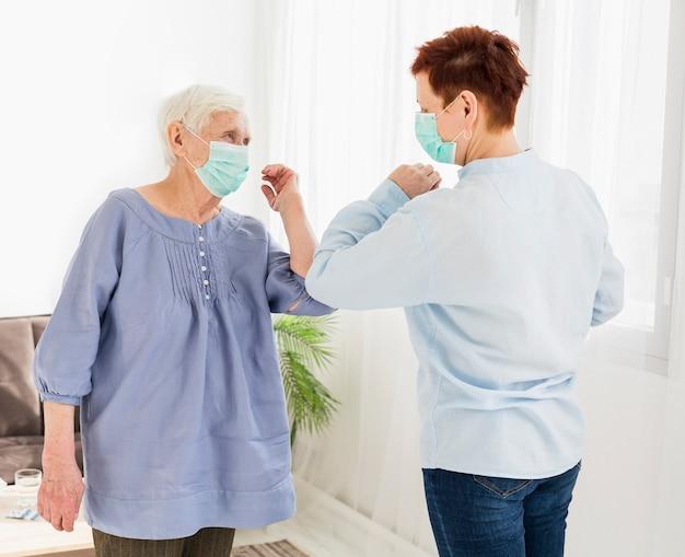 Вид сбоку пожилых женщин, приветствующих друг друга касанием локтей