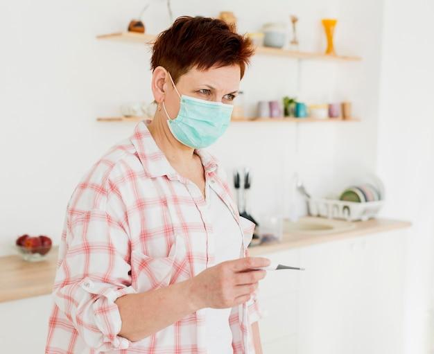 温度計を保持している医療マスクを持つ高齢者の女性の側面図