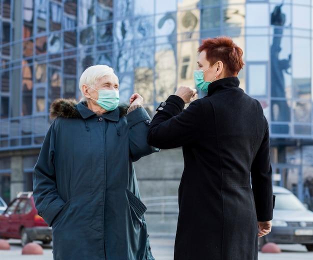 Пожилые женщины приветствуют друг друга в городе