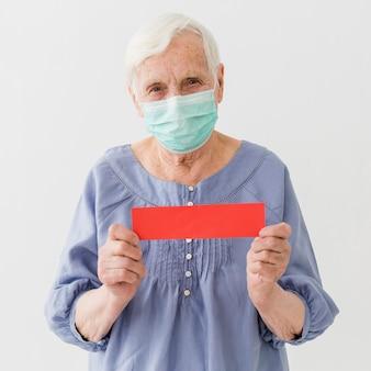 医療マスクを持つ年上の女性の正面図