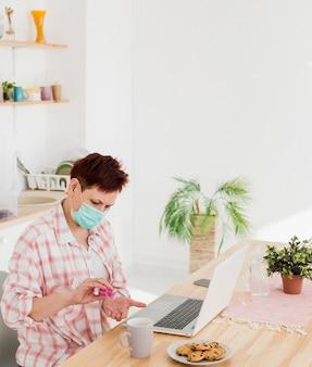 Вид сбоку старшей женщины, дезинфицирующей ее руки перед работой дома