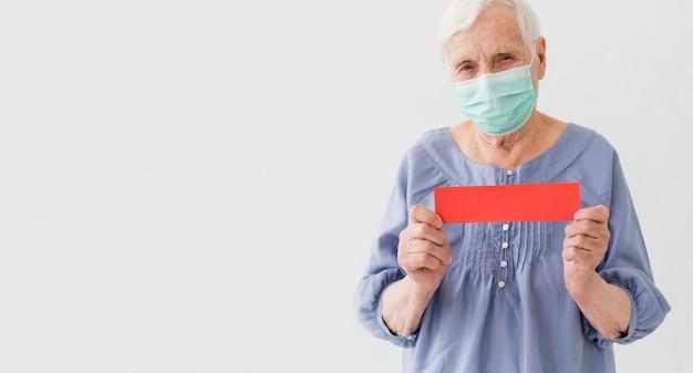 医療マスクとコピースペースを持つ高齢者の女性の正面図