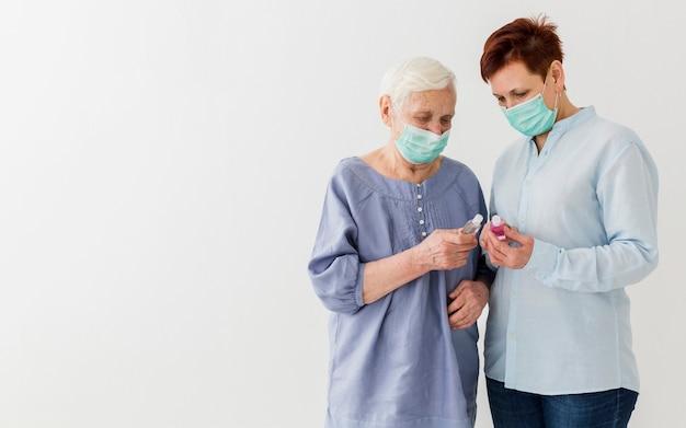 コピースペースを持つ手の消毒剤を保持している医療マスクを持つ高齢者の女性の正面図