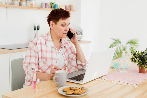 Вид сбоку старшей женщины разговаривает по телефону у себя дома
