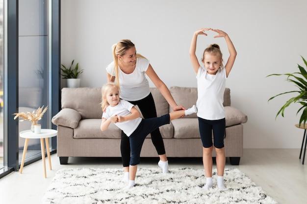 Дочери и мама тренируются дома