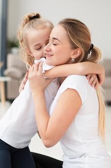Вид сбоку дочери, обнимая смайлик матери