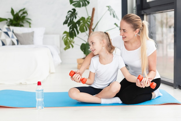 Вид спереди матери и дочери, осуществляя с весами в домашних условиях