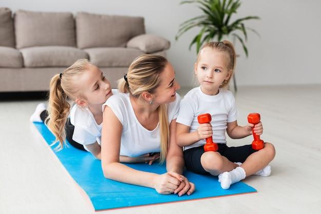 Мать позирует с дочерьми на коврик для йоги дома