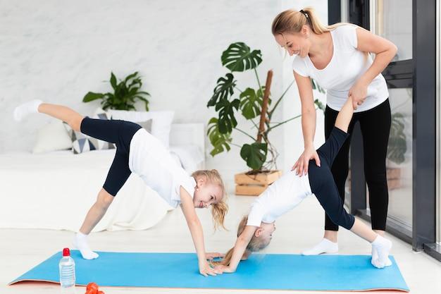 家で娘が運動するのを助ける母親