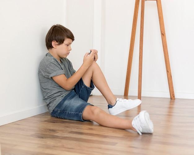 Молодой мальчик, играя на смартфоне