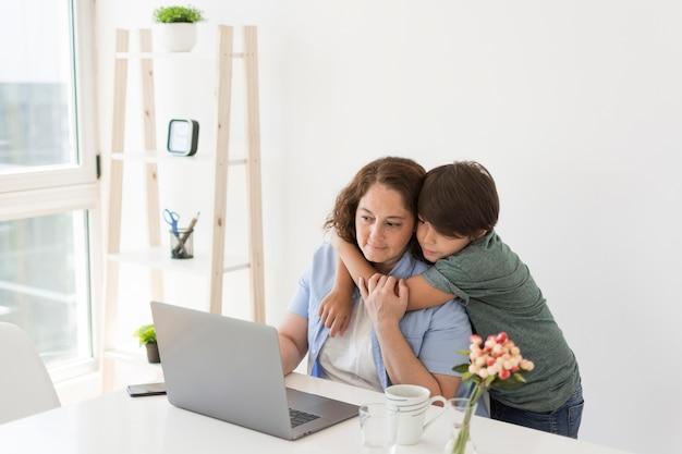 ラップトップに取り組んでいる子供を持つ母