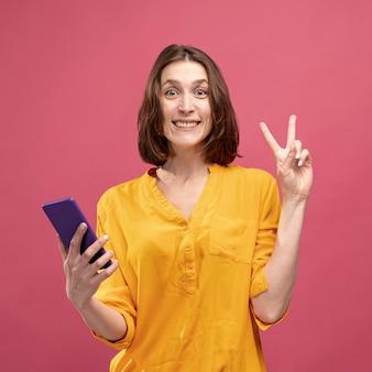スマートフォンを押しながらピースサインを作る笑顔の女性の正面図