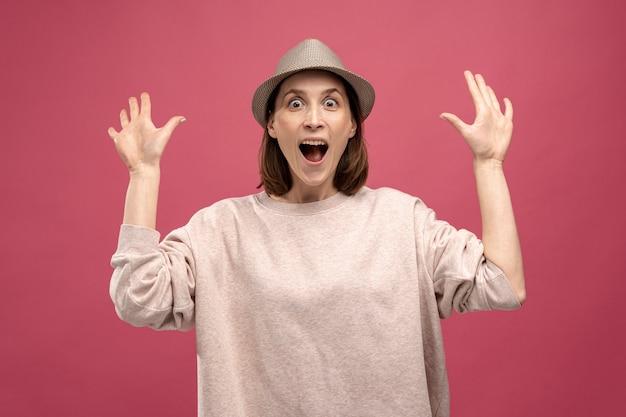 Вид спереди женщины в шляпе позирует в шоке