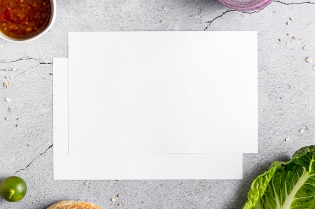 Плоская прокладка пустой бумаги меню на бетоне с овощами