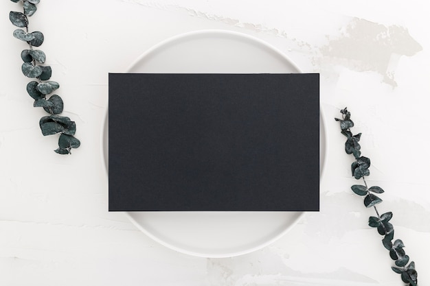 植物とプレートの空白のメニュー紙のトップビュー