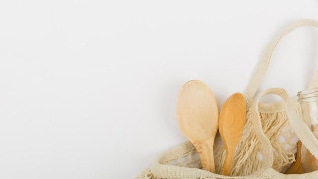 木製スプーンとコピースペースと再利用可能なバッグのフラットレイアウト