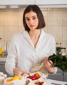 Портрет молодой женщины, позирует с органическими овощами