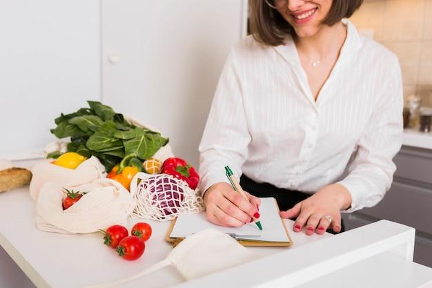食料品のリストをチェックする若い女性