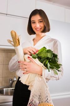 Портрет красивой женщины, держащей продукты