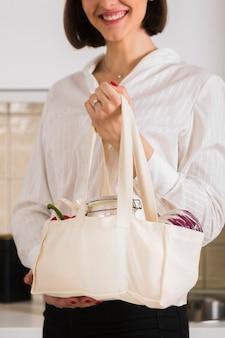 Портрет женщины, держащей мешок органических продуктов