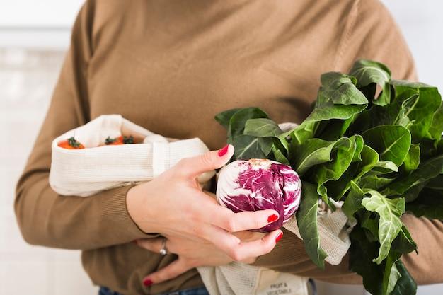 Крупным планом женщина, держащая органические овощи