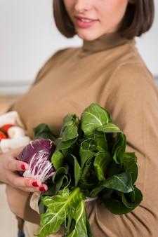 Крупным планом молодая женщина, держащая свежие овощи