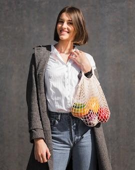 Портрет молодой женщины, держащей экологически чистую сумку