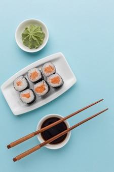 Вид сверху суши роллы с соевым соусом и палочками