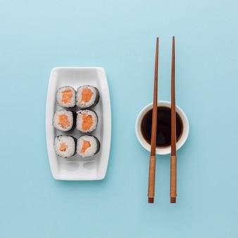 Вид сверху вкусные суши роллы с соевым соусом и палочками