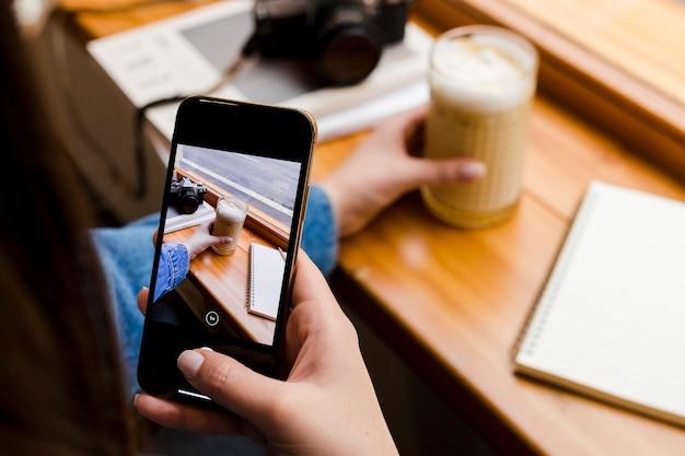 スマートフォンと一杯のコーヒーを持つ女性