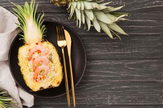 Вид сверху половинки ананаса со столовыми приборами
