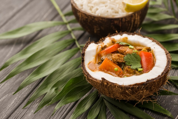 Половинки кокоса, заправленные тушеным мясом