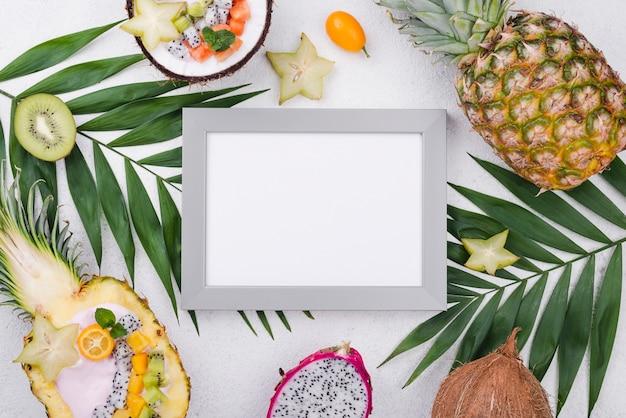 Пустая рамка в окружении экзотических фруктов