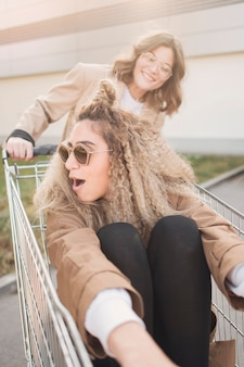 ショッピングカートで遊ぶ若い女性