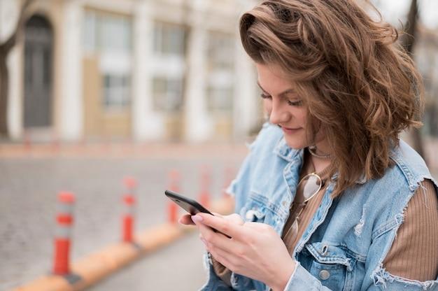 Стильный молодой подросток просматривает мобильный телефон