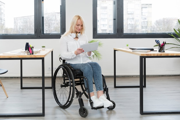 Вид спереди женщины в инвалидной коляске в офисе