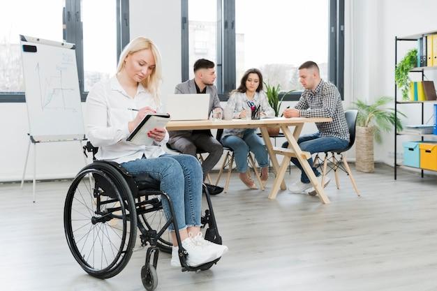 オフィスで車椅子の女性の側面図