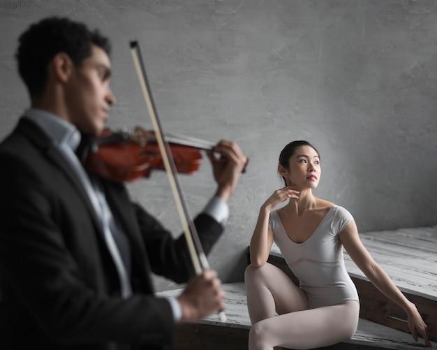 Балерина позирует как музыкант играет на скрипке