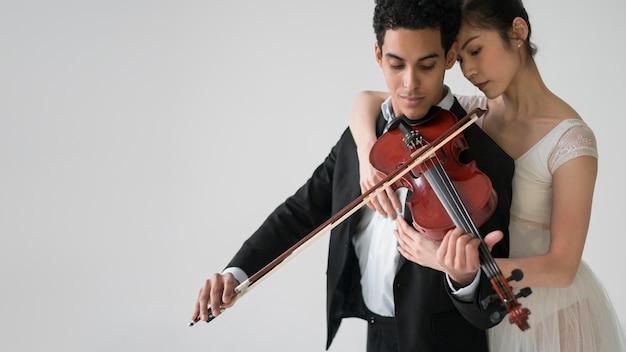 ミュージシャンがバレリーナとコピースペースでバイオリンを弾く