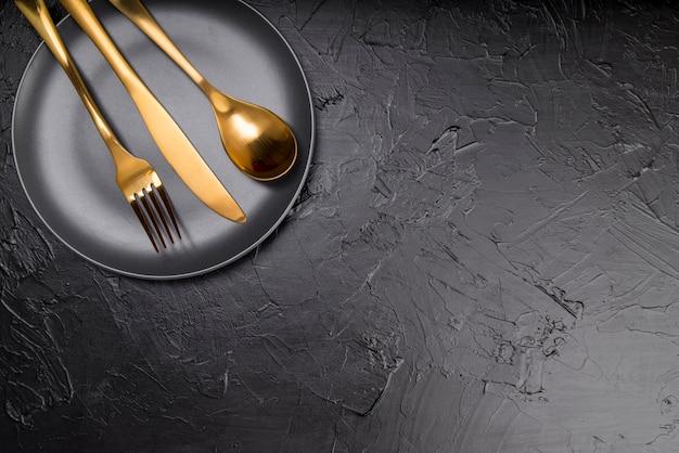 Вид сверху тарелки с золотыми столовыми приборами и копией пространства