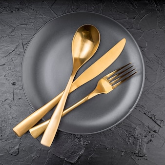 Вид сверху тарелки с золотыми столовыми приборами