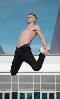 空中で踊る上半身裸のヒップホップの実行者の側面図