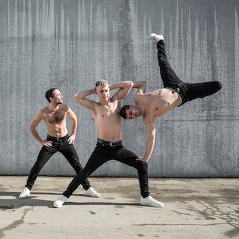 Вид спереди трех без рубашки исполнителей хип-хоп позирует на улице