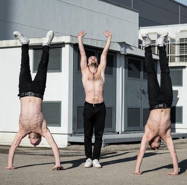 外のルーチンを練習している上半身裸のヒップホップの実行者の正面図
