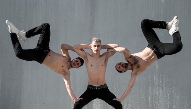 外で踊りながらポーズをとって上半身裸のヒップホップのパフォーマーの正面図